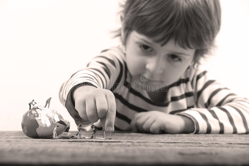 Peuter die op miniatuurmensen letten barstend een ei stock foto