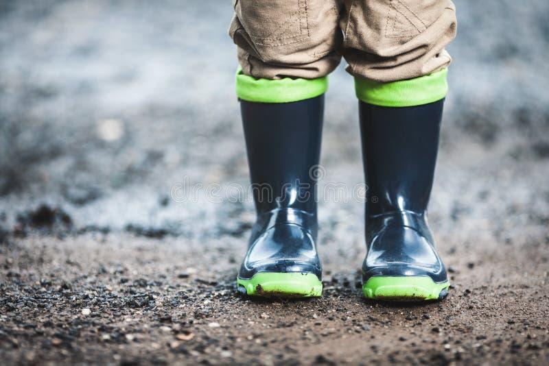 Peuter die rubberlaarzen in regenachtig weer dragen royalty-vrije stock foto's