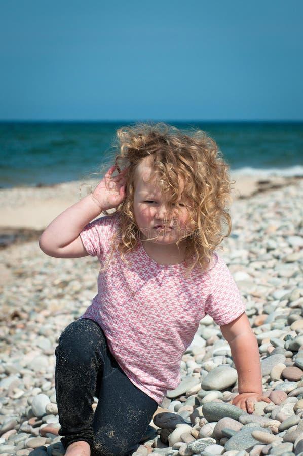 Peuter het spelen op a pebbled strand stock fotografie