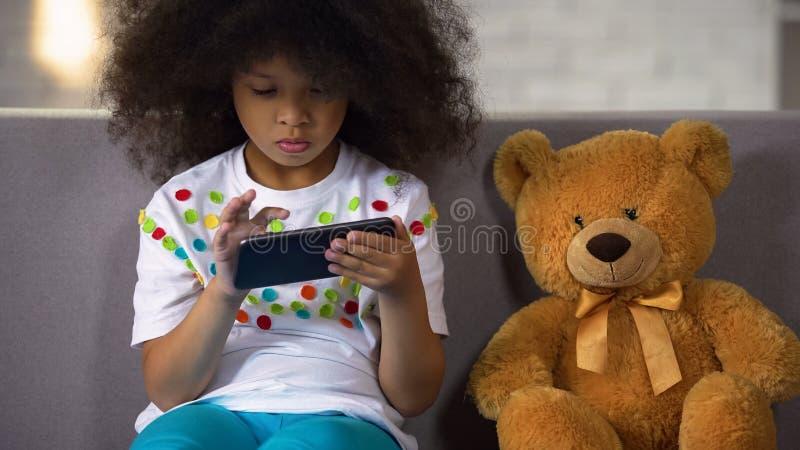 Peuter krullend Afrikaans meisje die brieven op smartphone bestuderen, onderwijsapps stock afbeeldingen