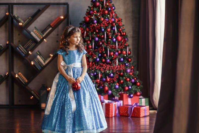 Peuter vrolijk weinig gelukkig meisje heeft thuis een goede tijd dichtbij heldere Kerstmisboom met lichten stock afbeelding