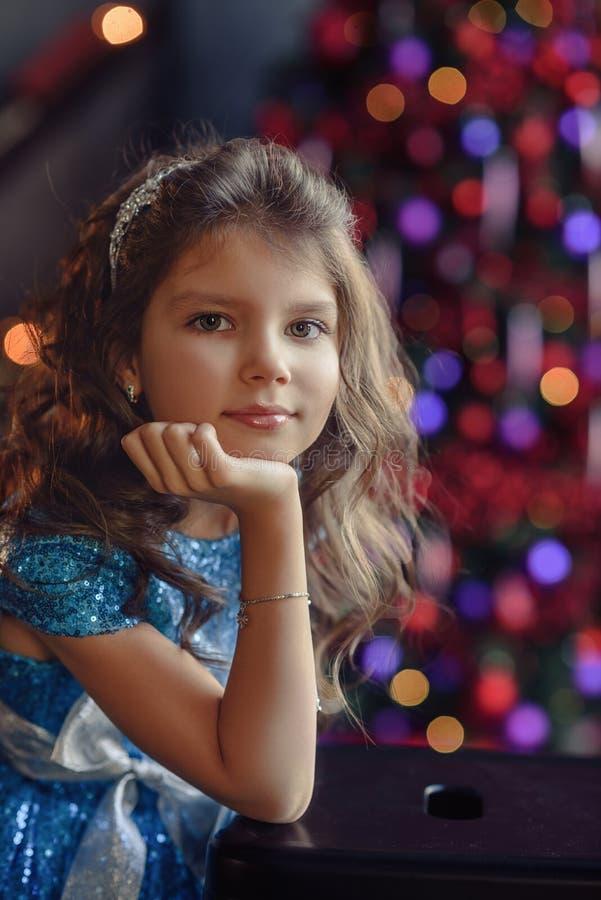 Peuter vrolijk weinig gelukkig meisje heeft thuis een goede tijd dichtbij heldere Kerstmisboom met lichten royalty-vrije stock foto