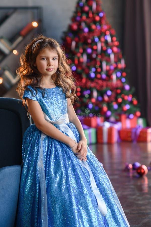 Peuter vrolijk weinig gelukkig meisje heeft thuis een goede tijd dichtbij heldere Kerstmisboom met lichten stock afbeeldingen