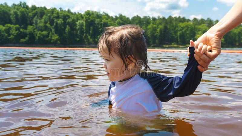 Peuterjongen die op een de zomerdag zwemmen stock fotografie