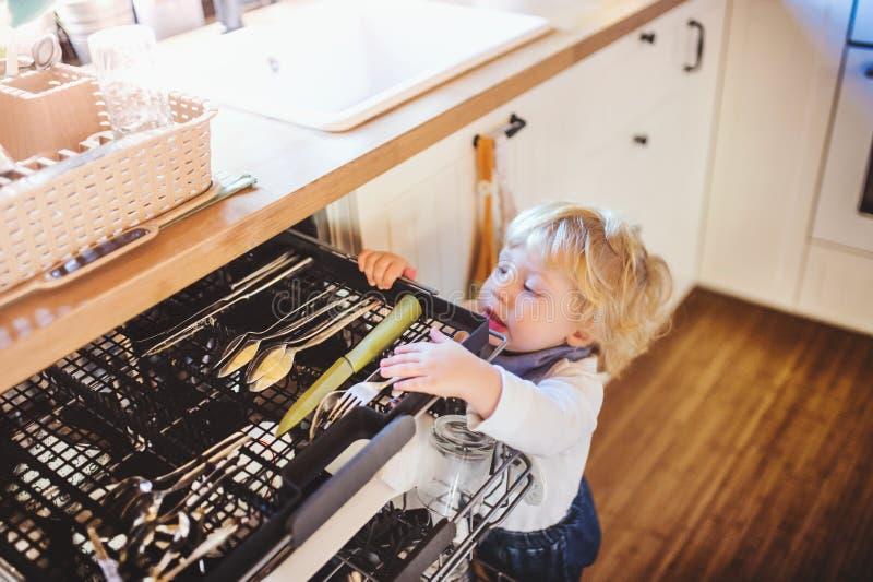 Peuterjongen in gevaarlijke situatie thuis Het concept van de kindveiligheid stock foto's