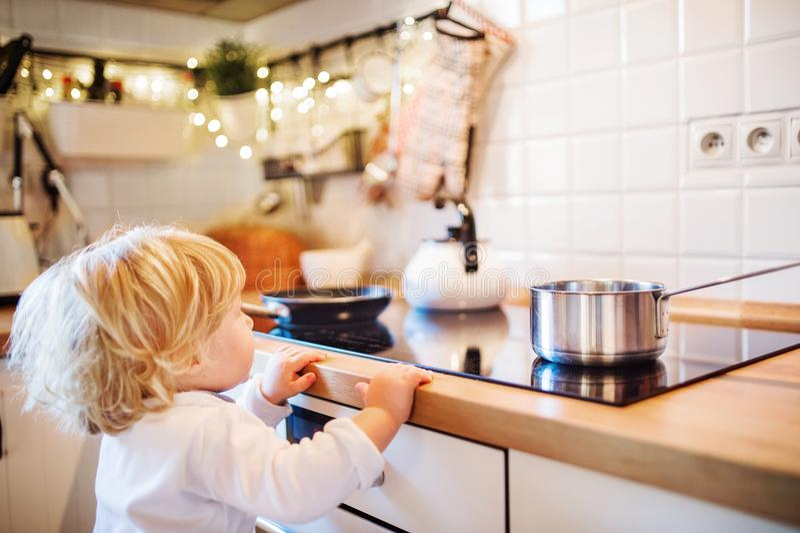 Peuterjongen in gevaarlijke situatie thuis Het concept van de kindveiligheid royalty-vrije stock afbeelding