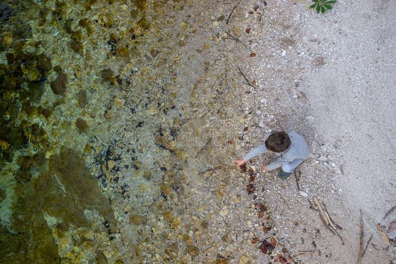 Peuterjongen het spelen door de rivier royalty-vrije stock foto