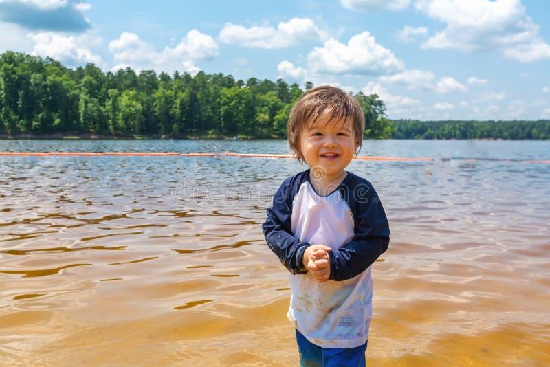 Peuterjongen het spelen in een meer op een de zomerdag stock afbeelding