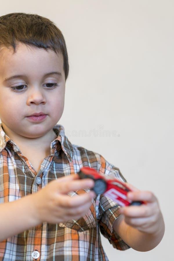 Peuterjongen met een rode stuk speelgoed auto De ruimte van het exemplaar Verticale foto royalty-vrije stock foto's