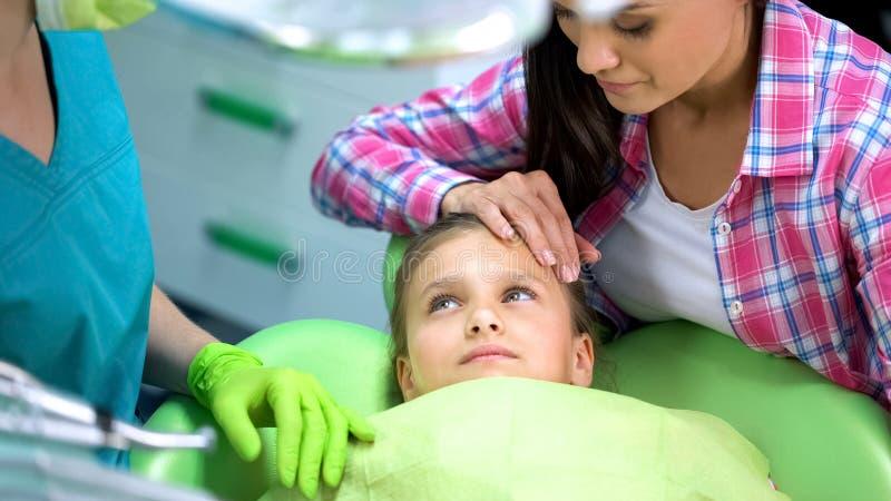 Peuterkind die tandarts, moeder het kalmeren vóór regelmatig onderzoek bekijken royalty-vrije stock foto