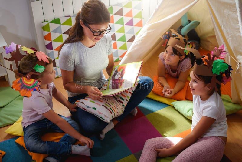 Peuterleraar die een verhaal lezen aan kinderen bij kleuterschool stock foto
