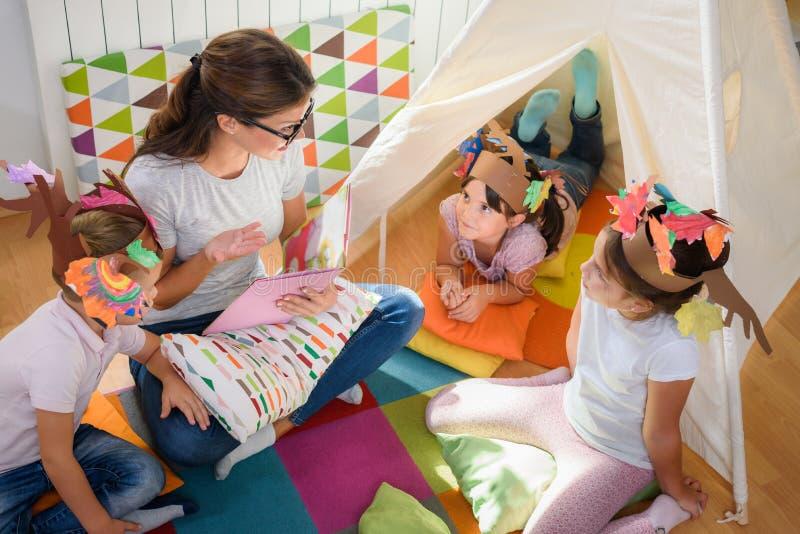 Peuterleraar die een verhaal lezen aan kinderen bij kleuterschool stock foto's