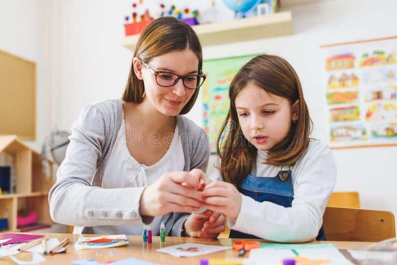Peuterleraar met kind bij Kleuterschool - Creatief Art Class stock afbeeldingen