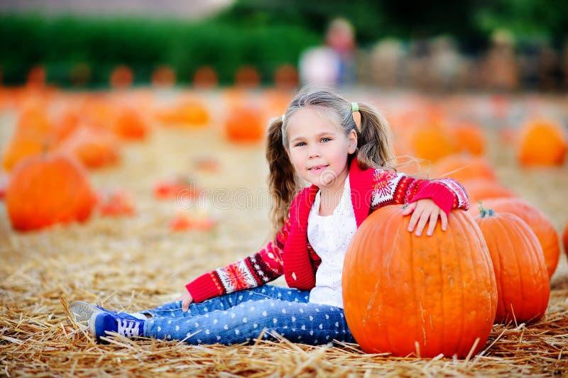 Peutermeisje die een pompoen plukken voor Halloween stock foto