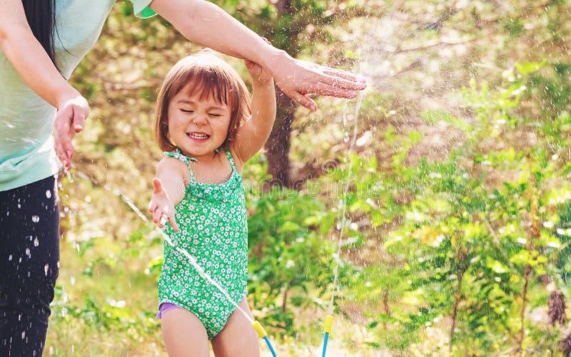Peutermeisje het spelen in een sproeier met haar moeder royalty-vrije stock foto