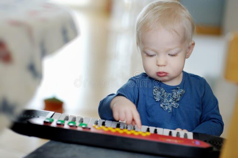 Peutermeisje het spelen stuk speelgoed piano royalty-vrije stock afbeelding