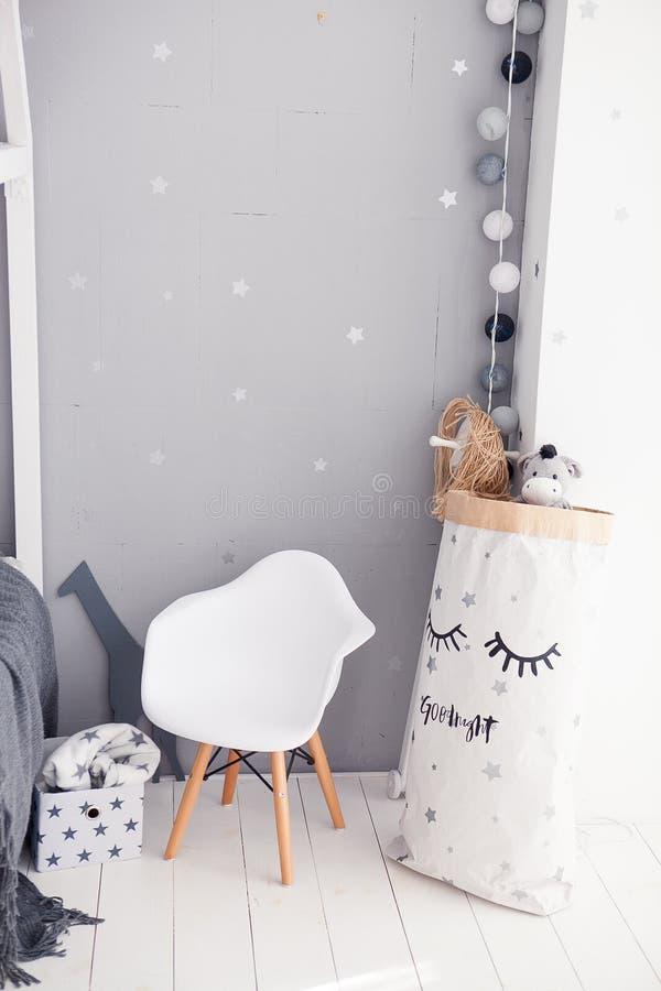 Peuterruimte met witte wieg, stoel en opslagzak royalty-vrije stock afbeeldingen