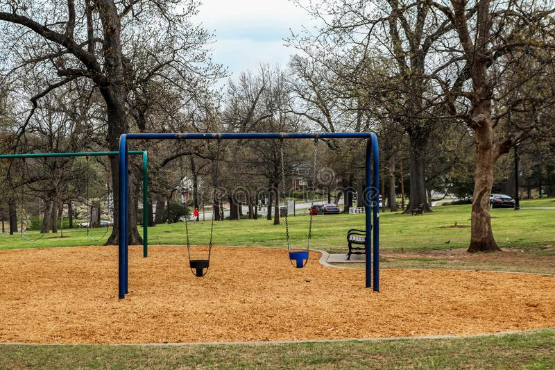 Peuterschommeling in stadspark met parkbank, persoon het lopen en vogels en eekhoorn en een paar auto's op de achtergrond - selec stock foto's
