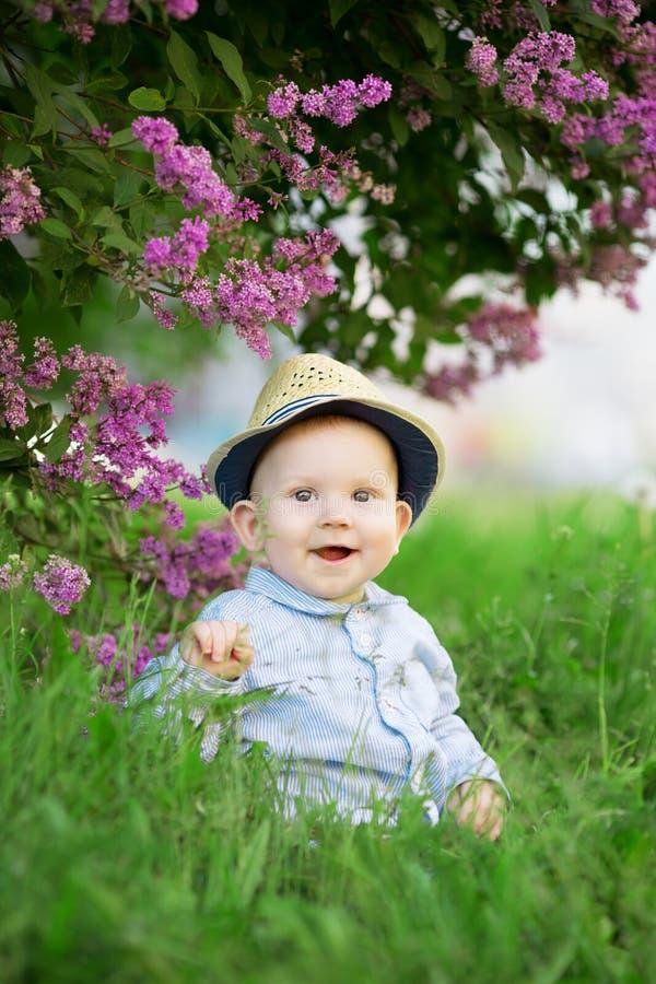 Peuterzitting op het gras in een weide Een baby op backgrou stock foto's