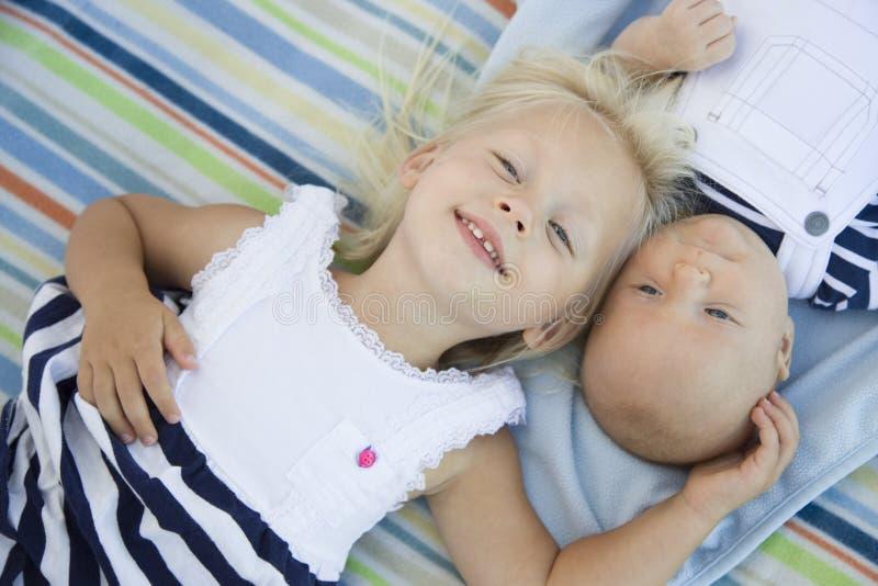 Peuterzuster Laying Next aan Haar Babybroer op Deken royalty-vrije stock afbeelding