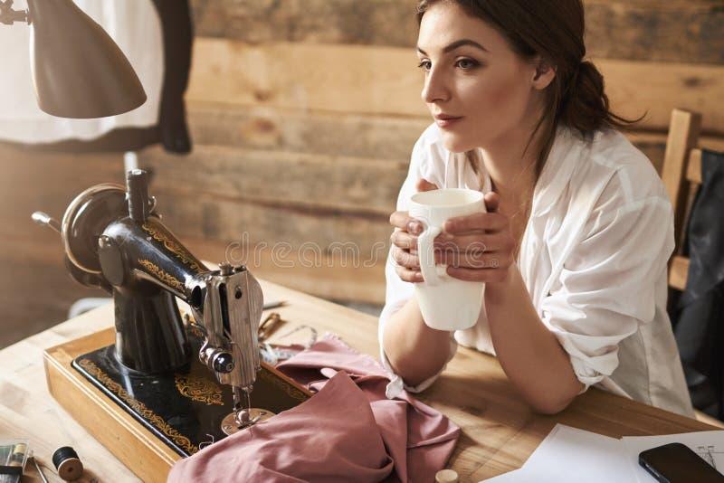 Pewnego dnia zostać sławną mój mody linia Marzycielski kobieta krawczyny główkowanie i pić kawa, siedzi blisko szwalnej maszyny zdjęcia royalty free