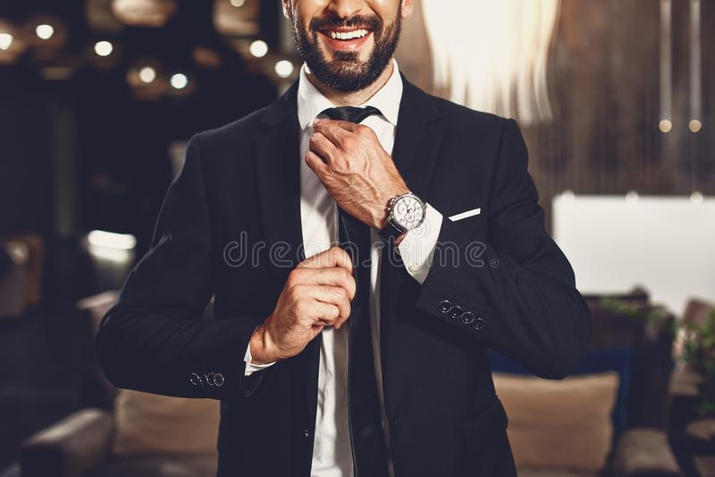 Pewny mÅ'ody czÅ'owiek dotykajÄ…cy krawata i uÅ›miechajÄ…cy siÄ™ stojÄ…c sam zdjęcia stock