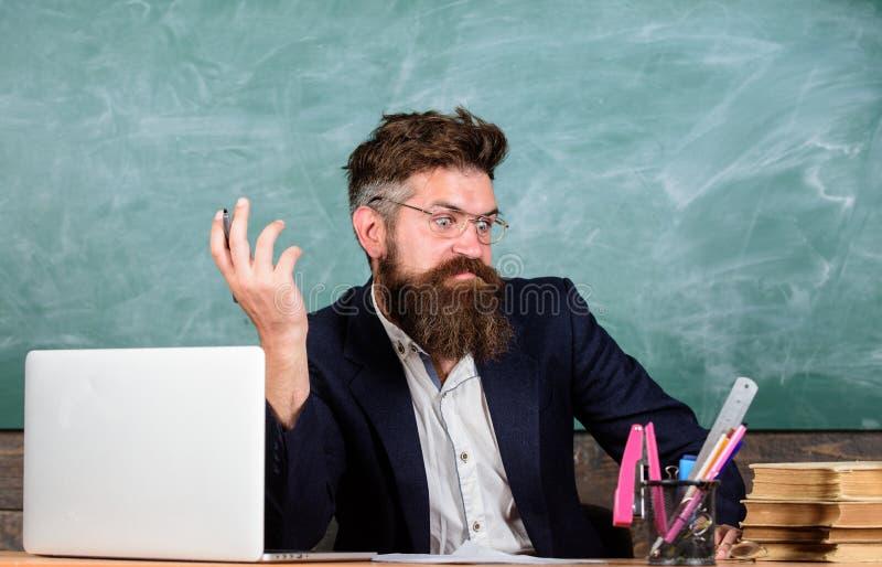 Pewny w wiedzie Egzaminator wątpienia pełno siedzi przy stołowym chalkboard tłem Chytry examinator ono waha się wokoło zdjęcia stock