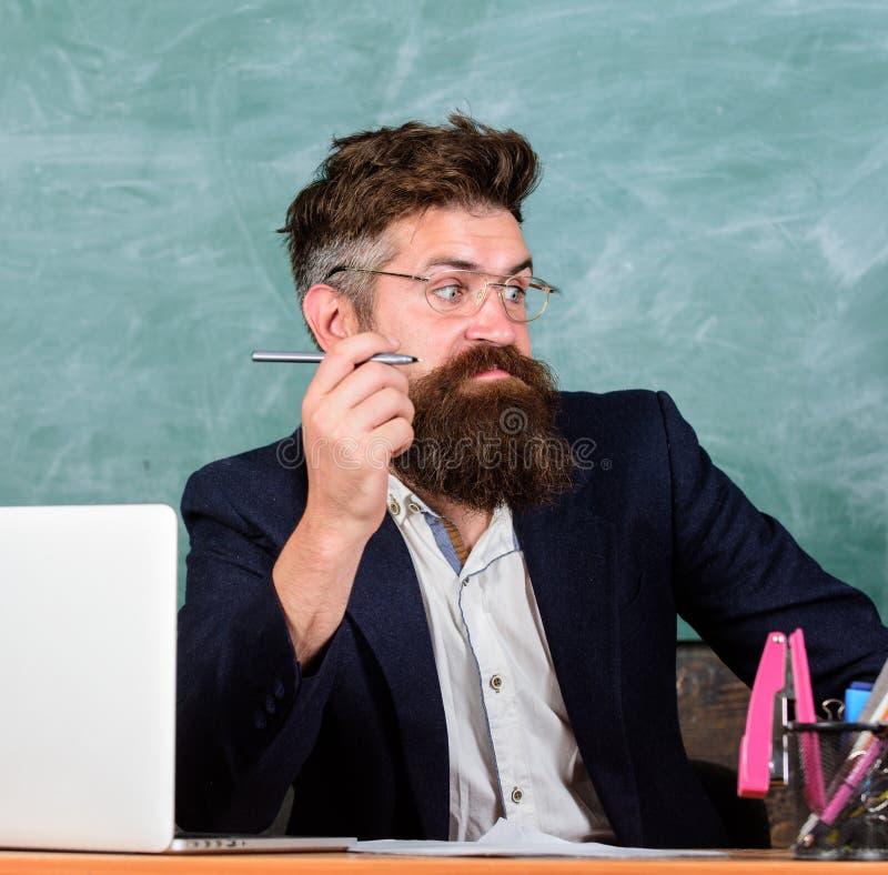 Pewny w wiedzie Egzaminator wątpienia pełno siedzi przy stołowym chalkboard tłem Szkolny egzaminu pojęcie chytry obrazy royalty free