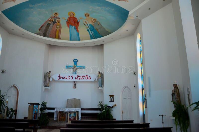 Pews pulpit statues and Jesus ceiling art Catholic Church of Holy Spirit Batumi Georgia. Batumi, Georgia - May 16, 2018: The interior of Batumi`s sole Catholic stock photo