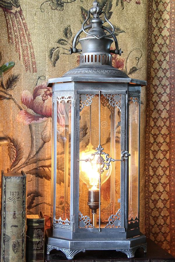 Pewter steampunk Edison lamp. A pewter color tin lamp with Edison bulb and steampunk styling against unique backdrop stock photos