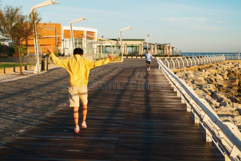 PEZARO, ITALIË - SEPTEMBER 21, 2012: Toeristen die ochtendjogging langs kust doen royalty-vrije stock foto's