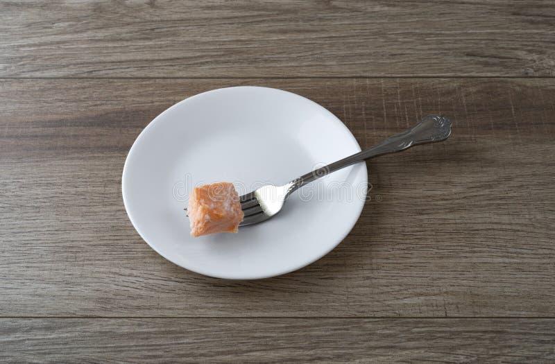 Pezzetto di salmone su un piatto bianco con una forcella immagini stock libere da diritti