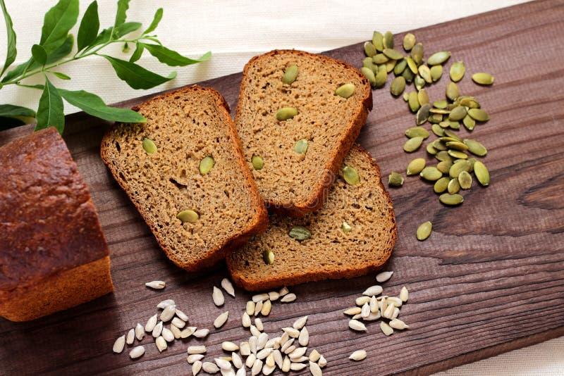 Pezzi affettati e un loa di bugia del pane di segale su un tagliere di legno immagine stock