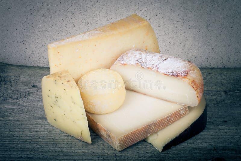 Pezzi capi e vari di formaggio su una tavola di legno tinto immagini stock