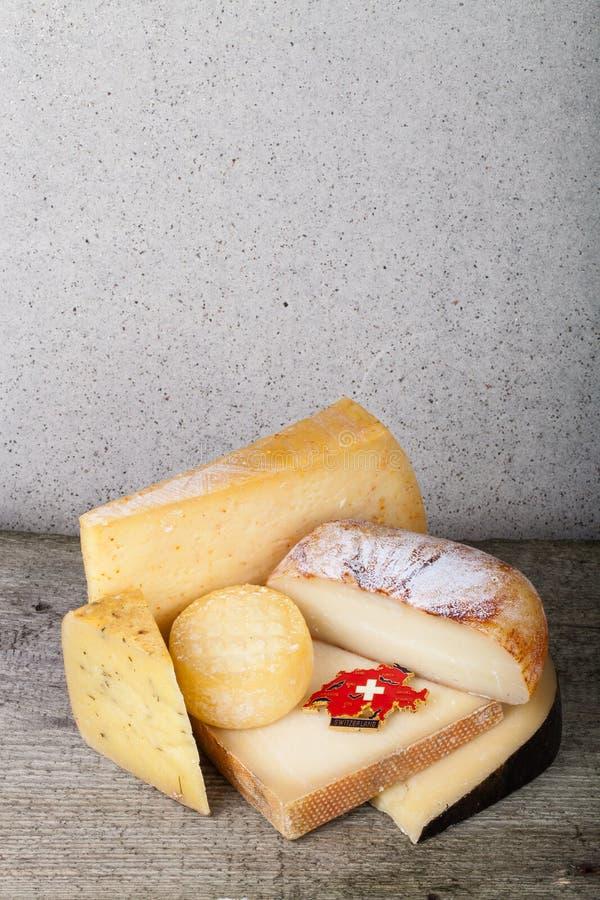 Pezzi capi e vari di formaggio su una tavola di legno verticale fotografie stock