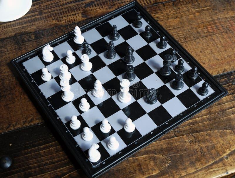 Pezzi degli scacchi in bianco e nero su una scacchiera, pegni che restano agai fotografie stock libere da diritti