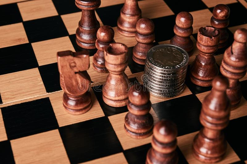 Pezzi degli scacchi con la pila delle monete sulla scacchiera immagini stock