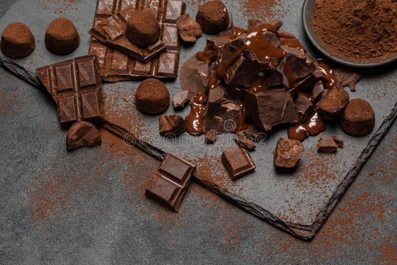 Pezzi del cioccolato al latte o di buio, sciroppo di cioccolato e caramelle del tartufo su fondo concreto scuro immagine stock