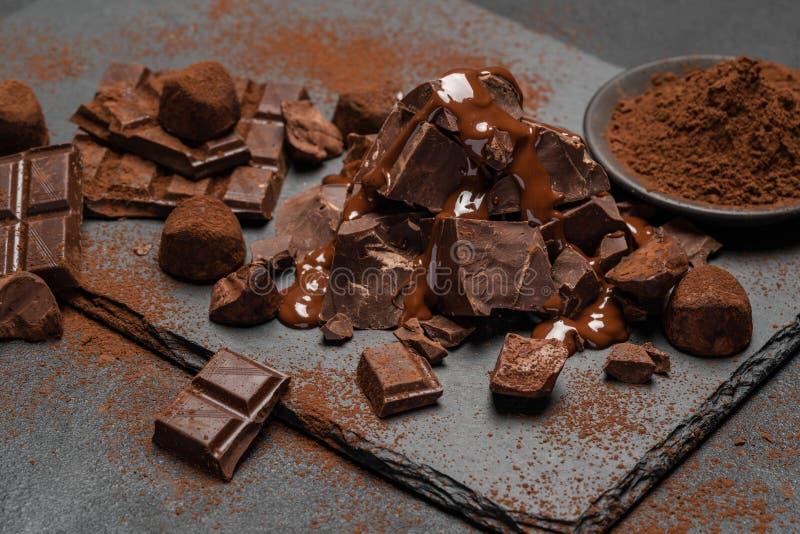Pezzi del cioccolato al latte o di buio, sciroppo di cioccolato e caramelle del tartufo su fondo concreto scuro fotografia stock
