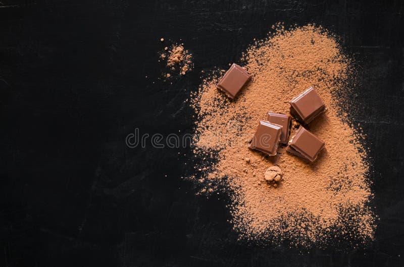 Pezzi del cioccolato con cacao in polvere su fondo scuro immagini stock