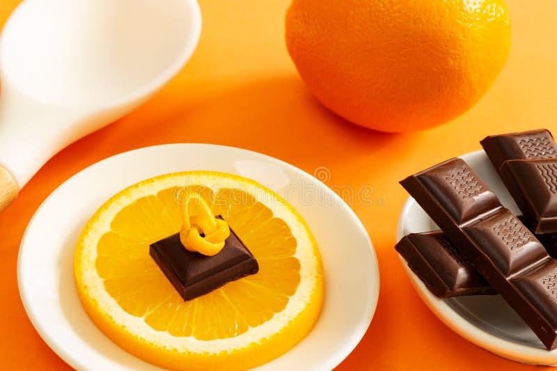 Pezzi del cioccolato sopra la fetta arancio, cucchiaio di cottura arancio e bianco pieno sopra fondo arancio fotografia stock