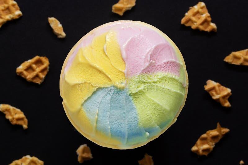 Pezzi del cono del gelato e della cialda su fondo nero Concetto zuccherato dolce non sano dell'alimento immagine stock