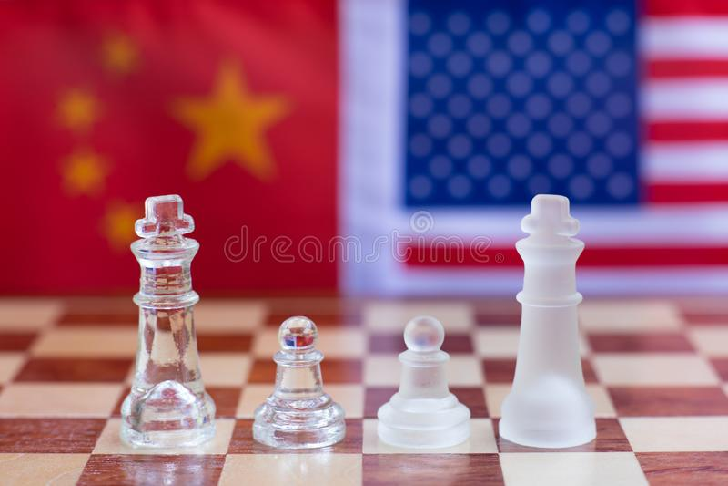 Pezzi del gioco di scacchiera su U.S.A. e sul fondo della bandiera della Cina, concetto di situazione di tensione della guerra co fotografia stock libera da diritti