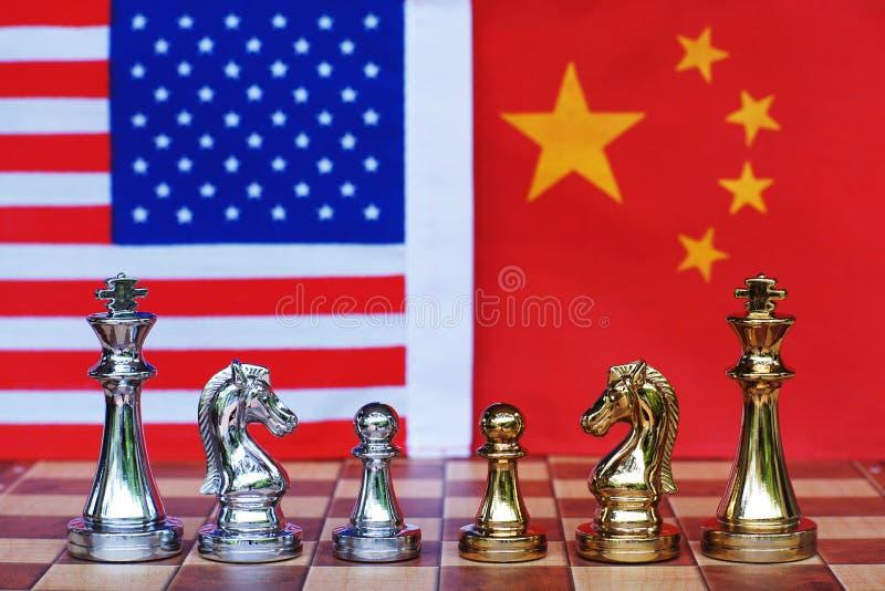 Pezzi del gioco di scacchiera su U.S.A. e sul fondo della bandiera della Cina, concetto di situazione di tensione della guerra co immagine stock libera da diritti