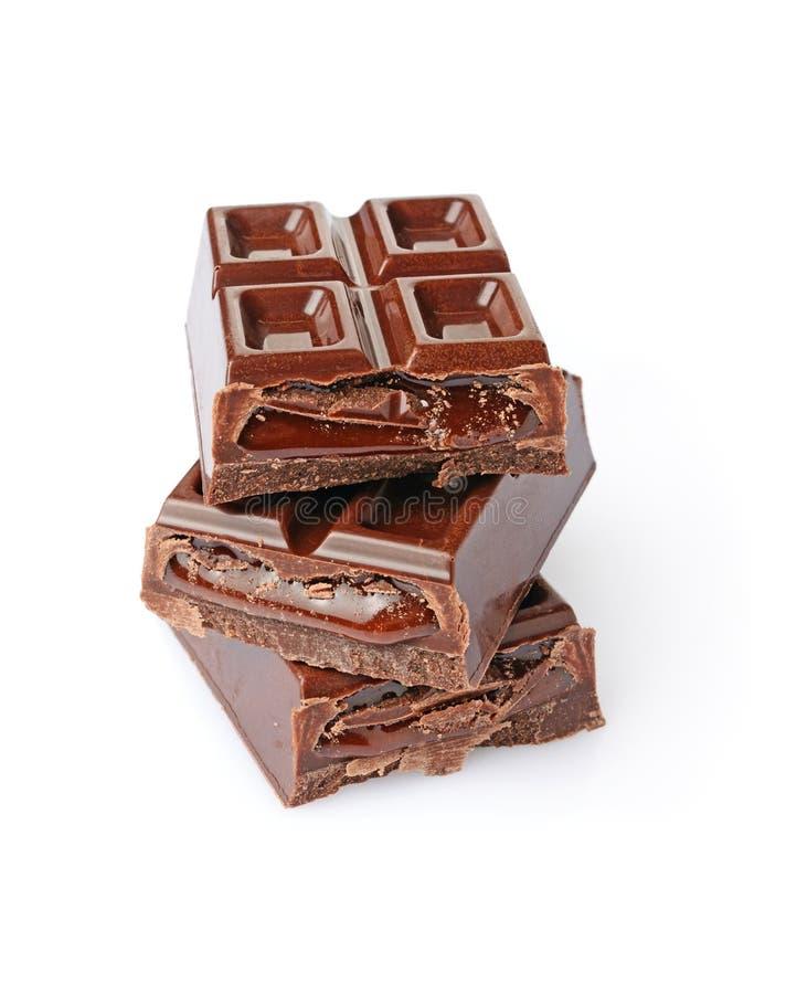 Pezzi del primo piano di barra di cioccolato con il riempimento del cioccolato liquido fotografie stock libere da diritti