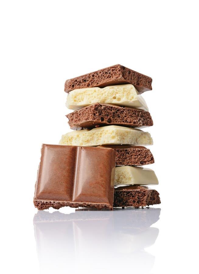 Pezzi del primo piano di barre del cioccolato al latte e di bianco poroso fotografia stock