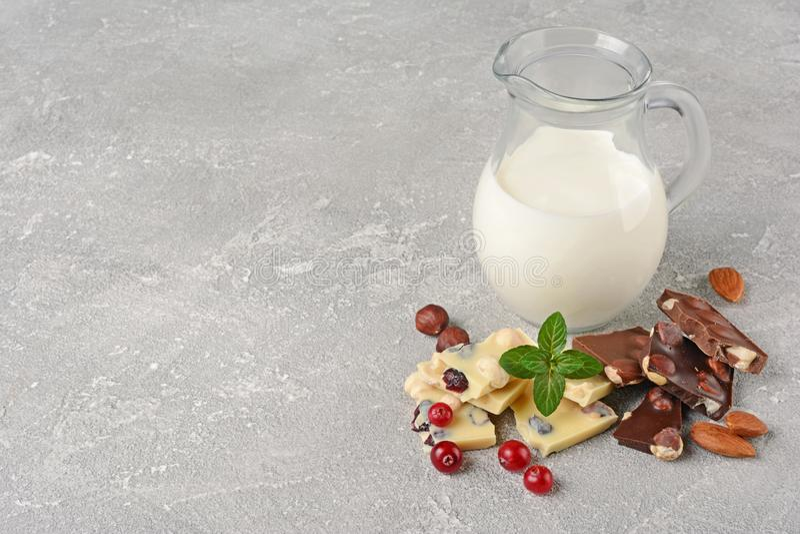 Pezzi del primo piano di bianco e barra di cioccolato fondente con le intere nocciole, mirtillo rosso, brocca del ½ del ¿ del and fotografia stock
