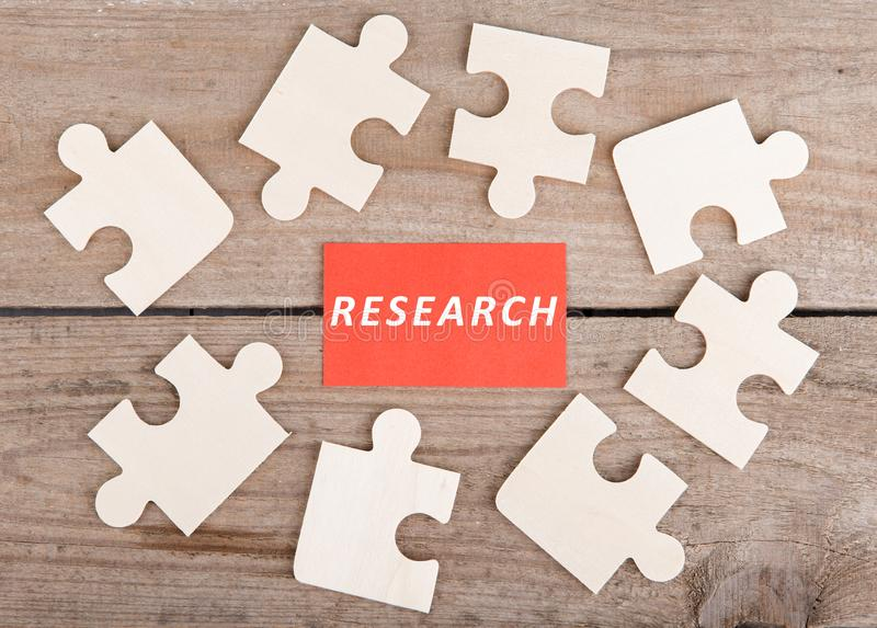 Pezzi del puzzle con testo & x22; Research& x22; su fondo di legno immagine stock