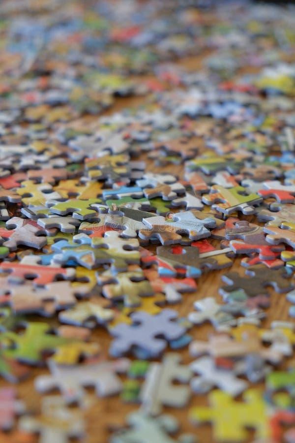 Pezzi del puzzle sparsi attraverso un ripiano del tavolo fotografia stock