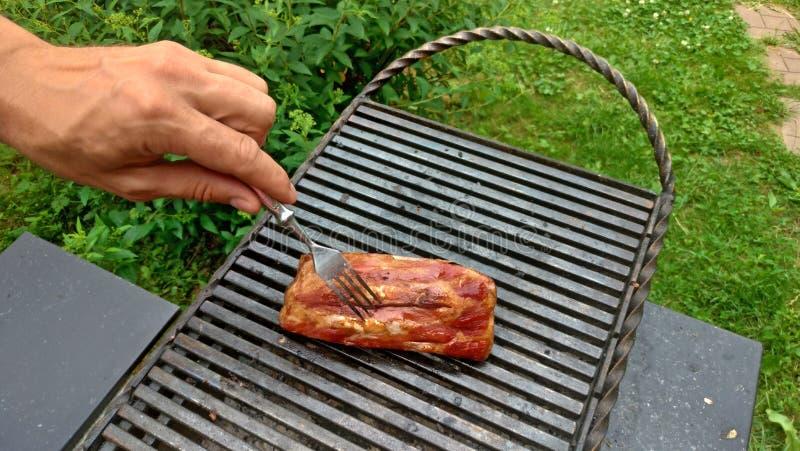 Pezzi deliziosi della carne di taglio di agnello con l'osso che è grigliato sotto le fiamme Costole saporite sulla griglia La man fotografie stock libere da diritti